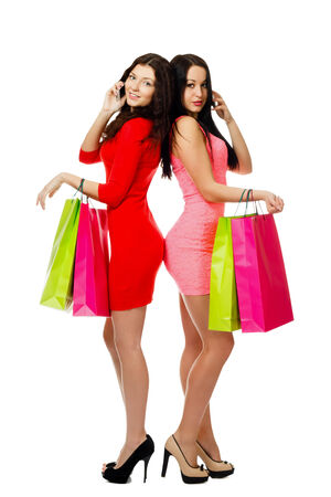 two young shopping women with bag talking by phone Stock Photo