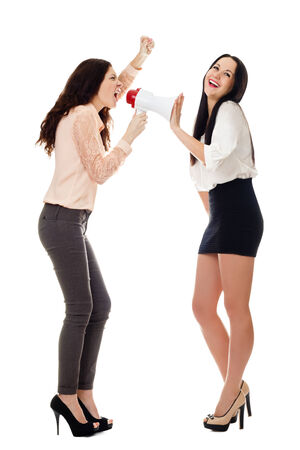 two smiling young standing women crying in megaphone isolated on white background