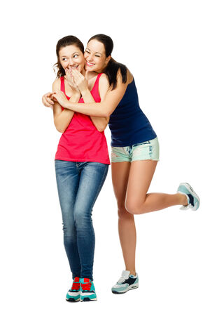 two young stand embracing and laughiing women isolated on white background