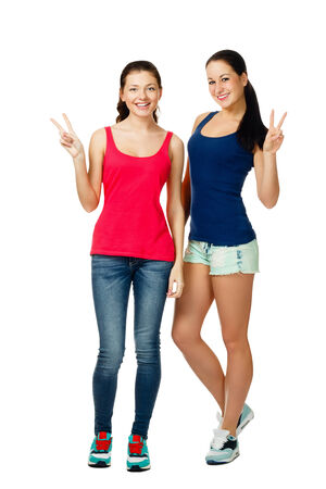two smiling young women sitting and showing victory sign