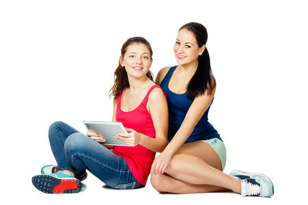 two beautiful young sitting women with pad