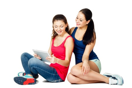 two beautiful young sitting women looking in pad