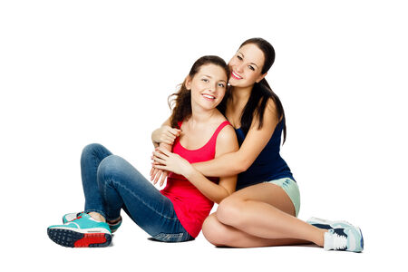 two young  sitting embracing  and laughing women isolated on white background