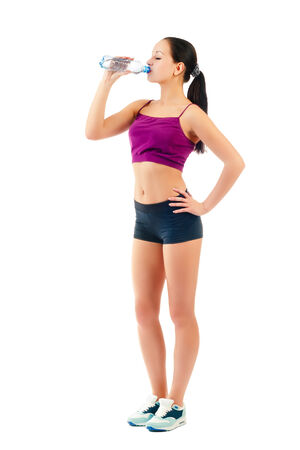 young sportswoman drinks water from bottle Stock Photo