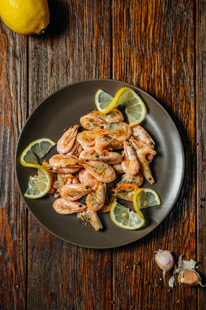 Plate of fried prawns on table, top view. Food on dark wood background. Stock Photo