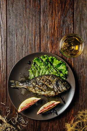 Grilled fish and glass of wine