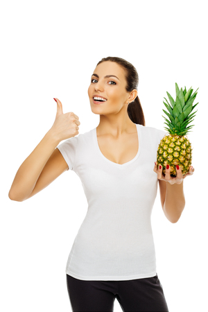 beautiful young happy brunette woman in white t-shirt holds pineapple. stands posing smiling on white background