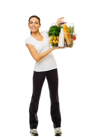 Young sporty brunette girl holding basket of food, fresh fruit and vegetables. In full growth. on white background