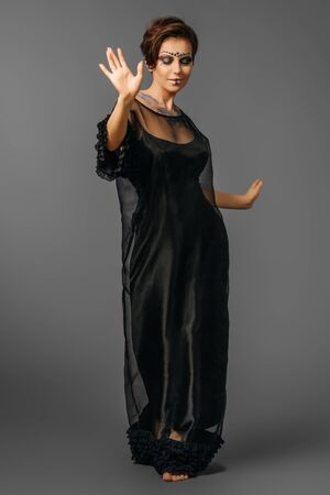 girl in black dress with unusual space makeup gracefully dancing posing on a gray background