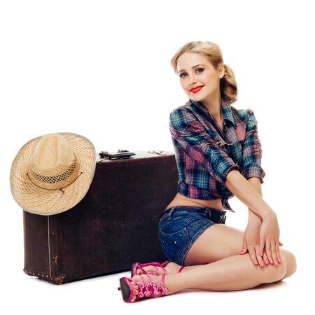 chica rubia con camisa a cuadros y pantalones cortos de mezclilla está sentada cerca de una vieja maleta con sombrero de paja y sonriendo juguetonamente a la cámara. aislado sobre fondo blanco Foto de archivo