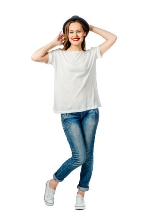 young cheerful girl in jeans, white t-shirt, sneakers and hat. isolated on white background