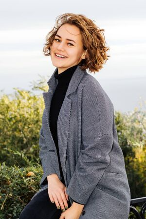 brown-haired girl smiling in gray coat against sky background