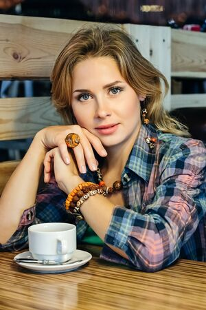 girl in a plaid shirt sitting in a cafe with a cup of tea Фото со стока