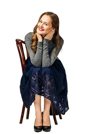young beautiful girl in blue skirt and gray jumper sitting with her head in both hands on old chair. isolated on white background Imagens