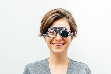 young smiling woman in optical trial frame on light gray background
