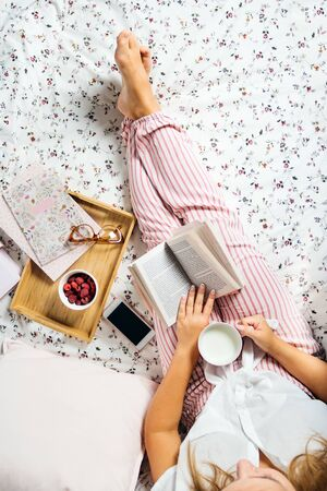 Young woman drinking milk at home in bed and reading book, top view vertically Archivio Fotografico - 133588790