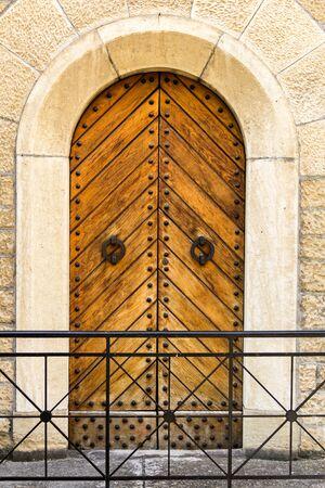 vintage wooden doors behind metal fence