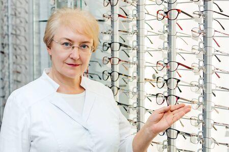 Professional senior female optician offering glasses in optics store Standard-Bild