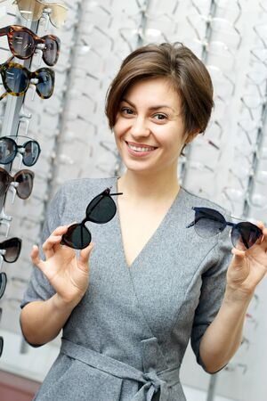 A young woman chooses on sunglasses in an optics store