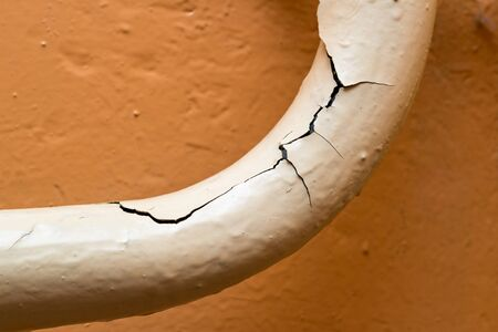 A peeling pipe against a yellow painted wall