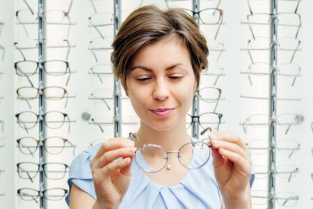 a smiling young female customer squints at the glasses in her hands in the store Banco de Imagens