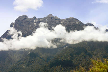 Mount Kinabalu in the afternoon surrounded by clouds
