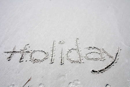 Word Holiday written in the sand