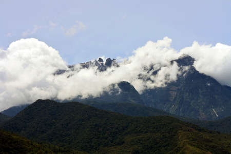 midst: Mount Kinabalu covered in the midst of clouds in mid-afternoon