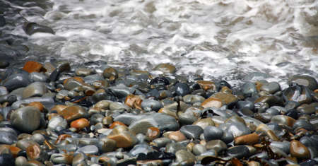 ocean waves receding from stones