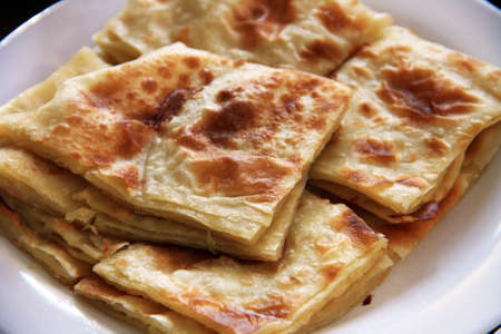 Roti Prata served on a plate cut into squares