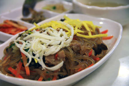 Japchae, Korean glass noodles with sides in the background