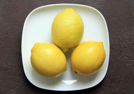 Three fresh lemons on a plate