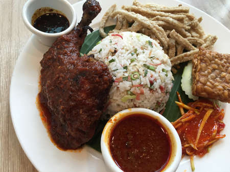 keropok: Traditional raw vegetable rice served with grilled chicken, fish crackers, mango chutney and sauces. Nasi ulam ayam bakar