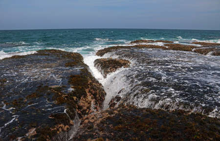 Incoming Tide over rocks and corals filling up crevices with water and surf Stock Photo