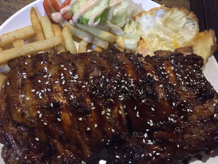 Delicious grilled pork ribs whole rack served with fries, salad and fried egg Stock Photo