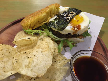 Ramen burger with egg and beef patty served with chips and sauce