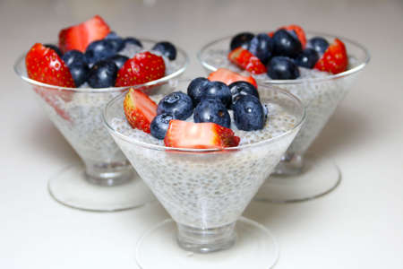 Three cups of chia pudding topped with blueberries and strawberries