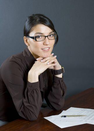 attractive businesswoman standing at her desk photo