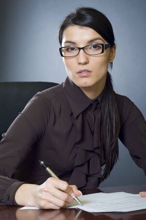 attractive businesswoman signing some documents photo