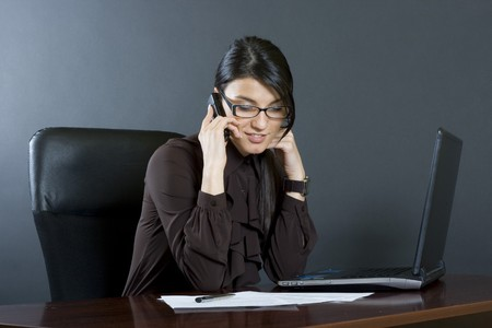 attractive businesswoman on the phone at her desk photo