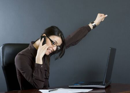attractive businesswoman talking on the phone and winning something photo