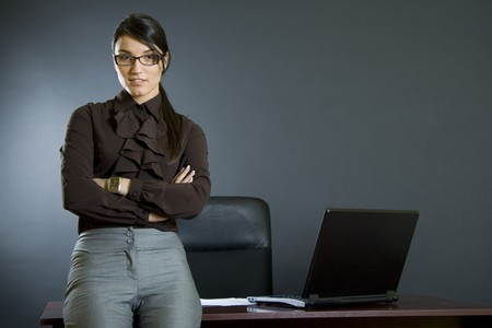 attractive business woman against desk Stock Photo