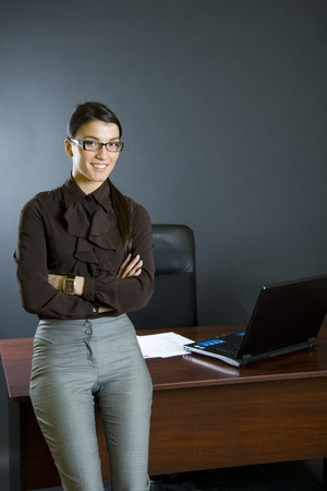 attractive business woman against desk with hands crossed photo