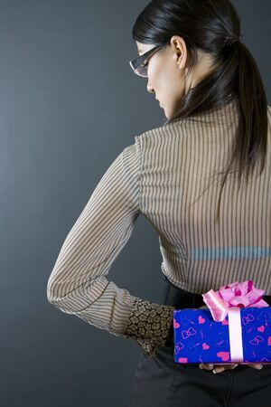 business woman holding a present at her back photo