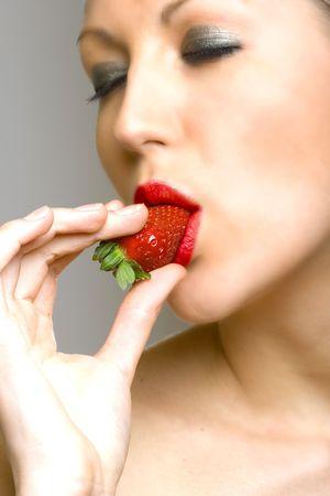 closeup of female face biting a strawberry Stock Photo - 4942292