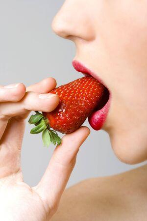 closeup of female face biting a strawberry Stock Photo - 4942434