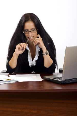 attractive businesswoman on her desk holding a pen Stock Photo - 5241253