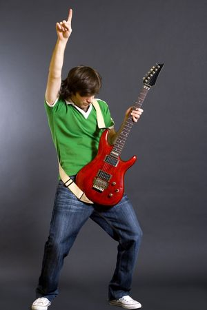 passionate guitar player playing his guitar with one hand up photo