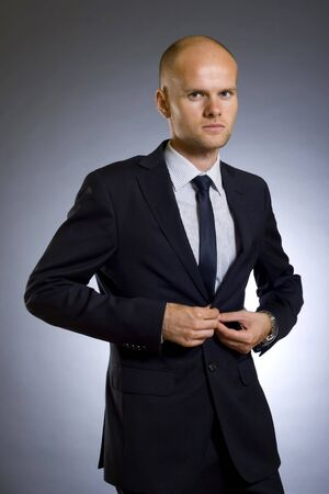picture of a young businessman buttoning his coat Stock Photo - 5511104