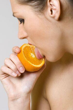 closeup of a woman licking an orange photo